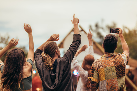 Photo for Rear view of young people at music concert. Group of men and woman raising hands and taking pictures at music festival. - Royalty Free Image