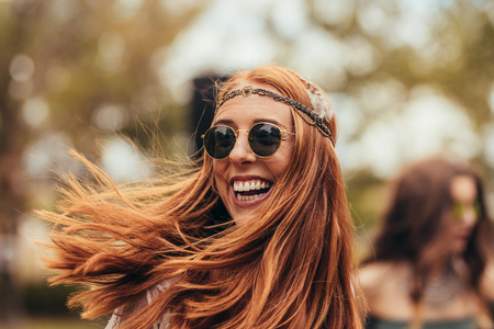 Foto de Caucasian woman in retro look enjoying at music festival. Beautiful young woman smiling in sunglasses at park. - Imagen libre de derechos