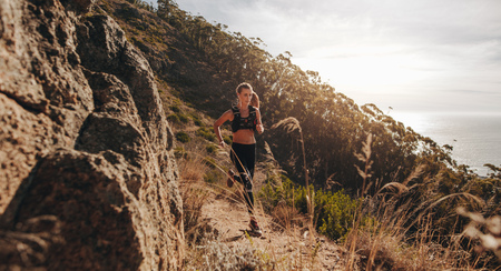 Photo for Woman running over extreme terrain on the hillside. Female runner training outdoors on rocky mountain trail. - Royalty Free Image