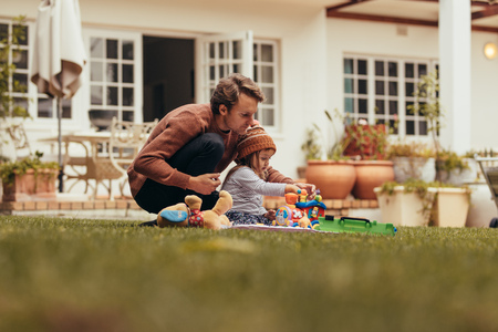 Photo pour Father and daughter sitting in the garden and playing with toys. Father and daughter spending time together sitting in their backyard. - image libre de droit