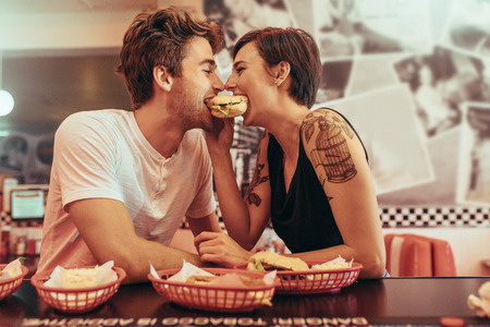 Photo pour Happy couple at a restaurant eating a burger together looking at each other. Man and woman sitting in a diner with food on the table sharing a burger. - image libre de droit