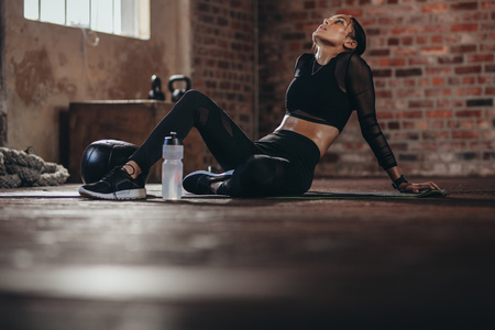 Photo for Tired woman having rest after workout. Tired and exhausted female athlete sitting on floor at gym with a water bottle. - Royalty Free Image