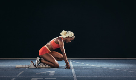 Foto de Female athlete taking position on her marks to start off the run. Side view of female runner  getting ready at the start line on running track on a black background. - Imagen libre de derechos