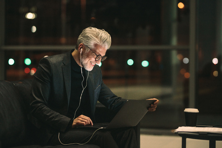 Photo for Smiling mature businessman working late on laptop in office lobby. Corporate professional looking at laptop and smiling. - Royalty Free Image