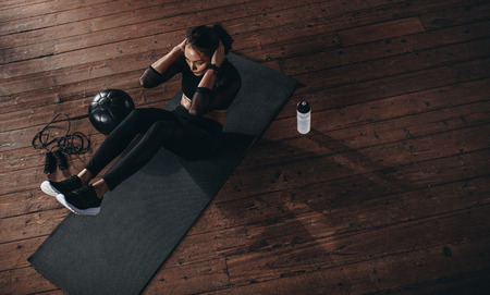 Photo for Top view of female doing abdomen workout at the gym. Fit woman on exercise mat with her hands behind head doing stomach exercises. - Royalty Free Image
