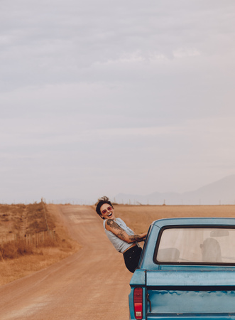Foto de Cheerful woman enjoying on travel vacation by a car on country road. Female sitting on car window and laughing. - Imagen libre de derechos
