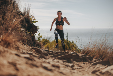 Foto de Fit woman running up the mountain trail. Female athlete practicing cross country running on a rocky trail. - Imagen libre de derechos