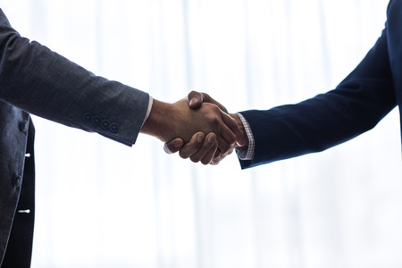 Photo for Close up of two business men shaking hands with each other after a deal, with focus on hand shake. - Royalty Free Image