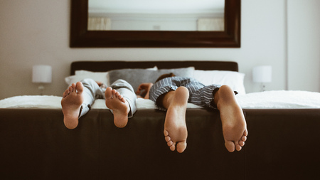 Foto für Feet of two people sleeping on bed. People sleeping on bed in different positions. - Lizenzfreies Bild