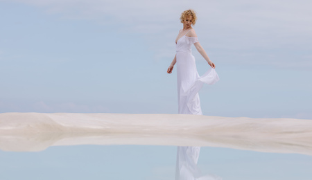 Photo for Woman in white gown standing at the beach with her reflection in water. - Royalty Free Image