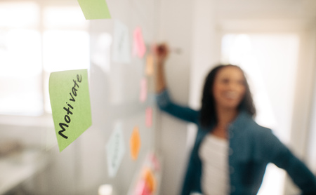 Photo for Blur image of a businesswoman pasting sticky notes on glass wall with focus on a post it note motivate written on it. - Royalty Free Image