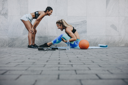 Photo pour Side view of woman doing sit ups while her friend relaxes with hands on knees. Two fitness women in happy mood while training outdoors. - image libre de droit
