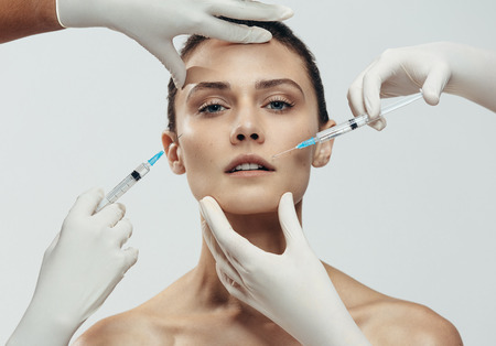 Photo pour Young woman gets injection in her lips and cheek by cosmetologists. Two beautician hands in gloves giving anti aging serum shot on female face against grey background. - image libre de droit