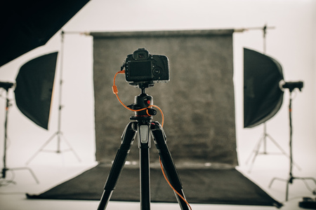 Photo for Studio setup with black background and studio flash lights with a DSLR camera on a tripod. - Royalty Free Image