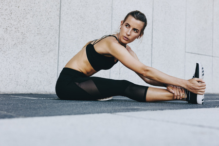 Foto de Fitness woman stretching her legs before workout sitting outdoors. Female runner doing stretching exercises listening to music. - Imagen libre de derechos