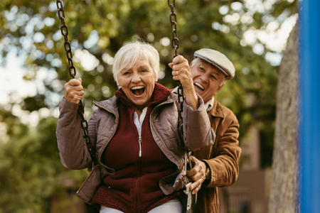 Foto de Senior man pushing his female partner on swing in park and having fun together. Playful and happy senior couple enjoying at swing in park . - Imagen libre de derechos