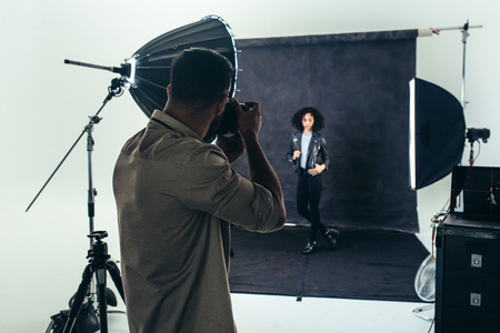 Photo for Model posing for a photograph during a photo shoot. Studio shot of a photographer shooting photos of a woman with studio flash lights on. - Royalty Free Image