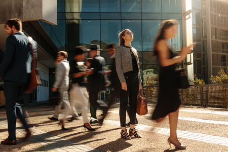Photo pour Businesswoman holding her hand bag standing still on a busy street with people walking past her using mobile phones. Woman standing amidst a busy office going crowd hooked to their mobile phones. - image libre de droit
