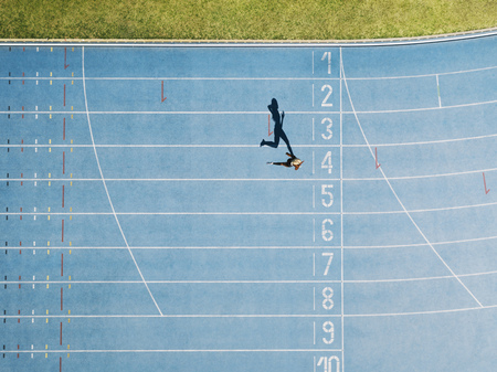 Photo for Female sprinter running on athletic track nearing the finish line. Top view of a sprinter running on race track in a stadium. - Royalty Free Image
