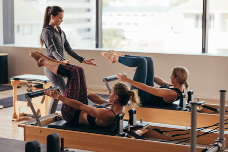 Photo pour Women doing pilates exercises lying on pilates workout machines while their trainer guides them. Two fitness women being trained by a pilates instructor. - image libre de droit