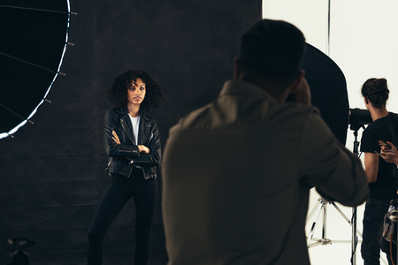 Photo for Rear view of a photographer taking photos of female model. Photographer with his team during a photo shoot. - Royalty Free Image