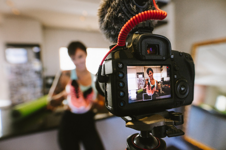 Photo for Female vlogger holding sports shoes in hands happily looking in camera while recording video for blog. Focus on camera with social media influencer reviewing and marketing a sports shoe. - Royalty Free Image