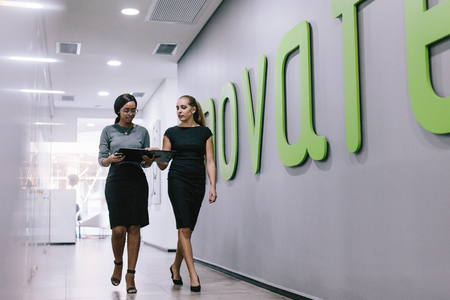 Foto de Two business women walking through office corridor and looking at a file. Business professionals discussing work in modern office hallway. - Imagen libre de derechos