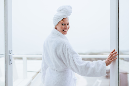 Photo for Smiling woman in a bathrobe with a towel wrapped on head. Rear view of a woman standing in balcony after her bath. - Royalty Free Image