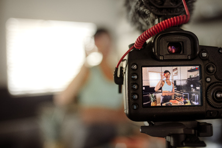 Photo for Camera screen showing woman holding a fruits in front of her eye in kitchen. Woman making a video for her blog on healthy eating. - Royalty Free Image