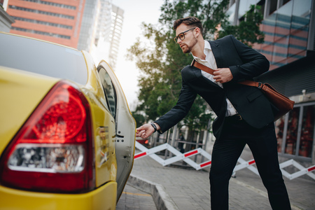 Photo for Entrepreneur opening the door of a taxi standing on the pavement. Man taking a taxi to go to office. - Royalty Free Image