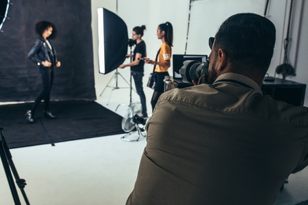 Photo for Female model posing for portraits on a black background in a studio. Photographer with his crew during a photo shoot in studio. - Royalty Free Image