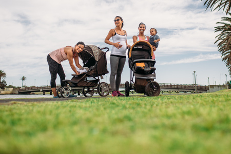 Photo pour Young mothers standing in a park with their babies in strollers. Active moms relaxing after morning walk in park with their kids. - image libre de droit