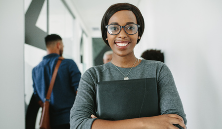 Foto de Portrait of cheerful african businesswoman wearing glasses standing in office with team in background. Smiling female executive with folder in office hallway with coworkers talking at the back. - Imagen libre de derechos