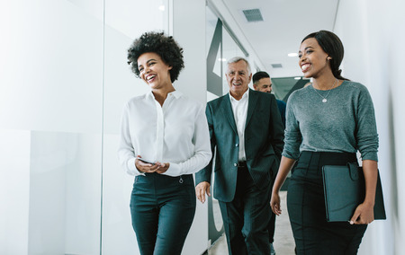 Foto de Diverse group of business people walking through office corridor.  Team of corporate professionals walking and talking in modern office hallway. - Imagen libre de derechos