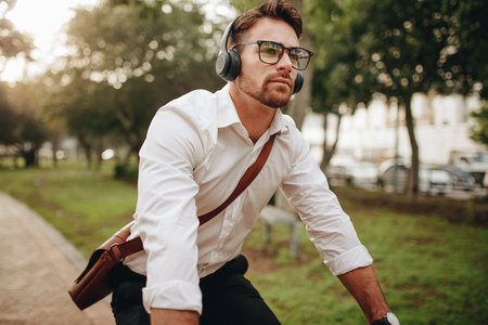Foto de Man commuting to office on a bicycle early in the morning. Man wearing office bag and wireless earphones riding a bicycle. - Imagen libre de derechos