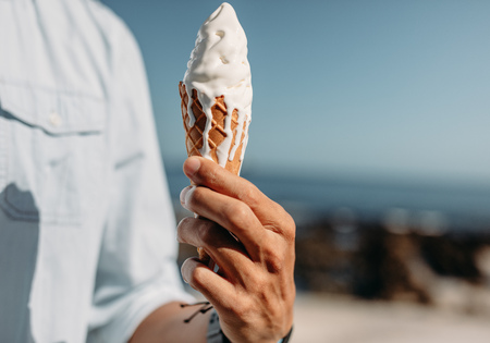 Foto de Close up of hand of man holding a melting ice cream cone. Man holding an ice cream on sunny day. - Imagen libre de derechos