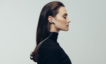 Foto de Side view of woman in black dress wearing earphones with eyes closed. Woman wearing earphones against grey background. - Imagen libre de derechos