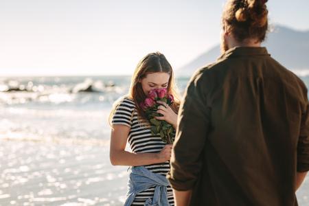 Foto de Beautiful woman smelling flowers on beach with boyfriend. Woman loving the surprise given by her boyfriend. Loving couple in beach. - Imagen libre de derechos
