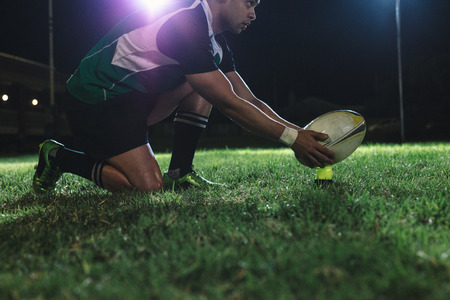 Photo for Rugby player placing the ball on tee for penalty shot during the game. Rugby player making a penalty shot under lights at sports arena. - Royalty Free Image