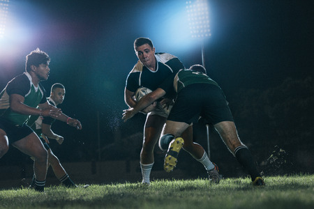 Foto per Strong rugby players fighting for the ball during the game. Intense rugby action under lights at sports arena. - Immagine Royalty Free