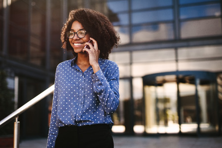 Photo pour Positive african woman in formal clothes walking outdoors and talking on smart phone. Female business professional making a phone call while walking outside with a building in background. - image libre de droit