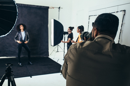 Photo for Photographer shooting photos of a model in a studio with his crew holding studio flash lights. - Royalty Free Image