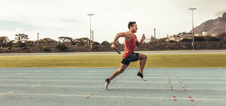 Photo for Side view of a male athlete sprinting on a running track in a track and field stadium holding a baton. Male runner training on a running track. - Royalty Free Image
