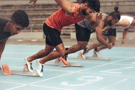 Photo for Runners using starting blocks to start the race on running track. Athletes starting their sprint on a running track with the help of starting blocks. - Royalty Free Image