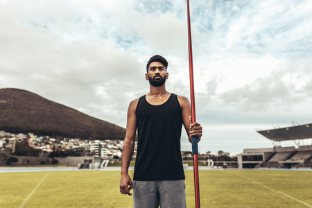 Photo for Athlete standing in a track and field stadium holding a javelin. Athlete training in javelin throw standing in a ground. - Royalty Free Image