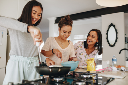 Foto de Young girls preparing breakfast in kitchen. Smiling girl cooking food while her friends help her in kitchen. - Imagen libre de derechos