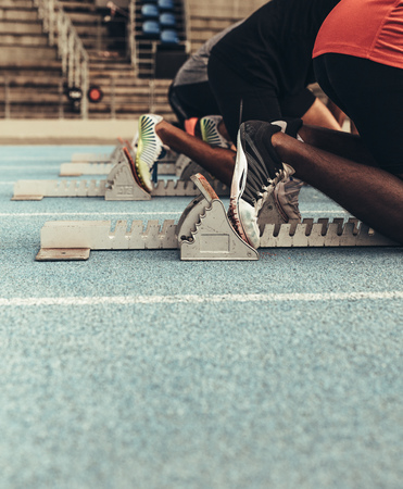 Photo for Sprinters on their mark ready to sprint on an all weather running track. Runners using a starting block to start their run on the race track. - Royalty Free Image