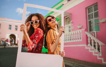 Photo pour Two women wearing colourful dress and sunglasses standing outdoors holding a photo frame with houses in background. Beautiful female friends enjoying outdoors with a blank picture frame. - image libre de droit
