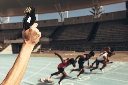 Foto de Close up of hand firing a starter pistol to start the running race. Athletes starting off for a race on a running track. - Imagen libre de derechos