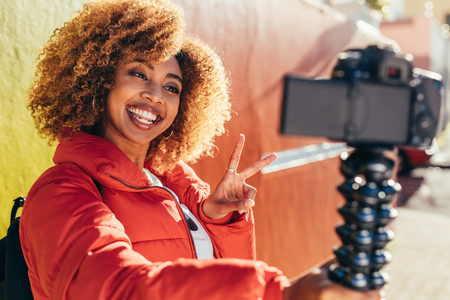 Photo pour Smiling afro american woman traveller taking a selfie using her digital camera. Smiling female tourist recording content for her blog outdoors holding a dslr camera showing victory symbol. - image libre de droit